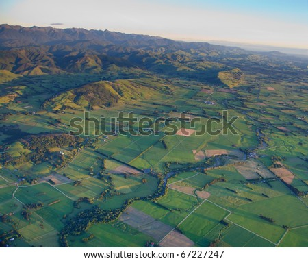 Aerial view of green paddocks, hills and mountains in the Wairarapa District, New Zealand