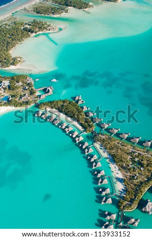 Aerial view of green water and bungalows - stock photo