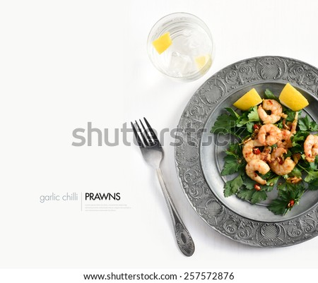 Aerial view of grilled chilli and garlic prawns on a bed of parsley with chillies and lemon garnish against a white background. Copy space. - stock photo