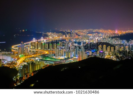 Aerial view of Haeundae beach with Gwangan bridge in Busan city at night, South Korea. Image contain of dust and noise. Beautiful Busan at night.