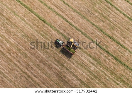 aerial view of harvest field with tractor and combine in Poland