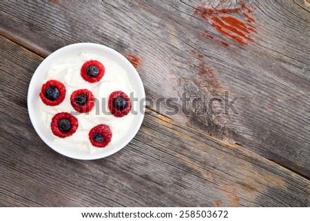 Aerial View of Healthy White Yogurt with Black and Red Berries Arranged on White Plate Placed on Rustic Wooden Table with Copy Space. - stock photo