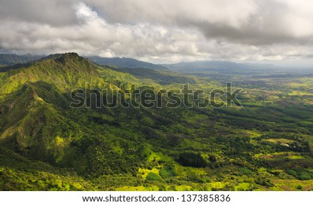 Aerial View of Kauai overlooking a green valley with a large mountain top - stock photo