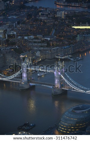 Aerial view of London at night. The river Thames, Tower Bridge and urban buildings in view.