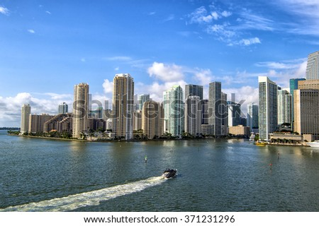 Aerial view of Miami skyscrapers with blue cloudy sky, boat sailing next to Miami downtown, horizontal picture - stock photo