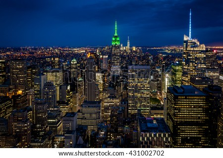 Aerial view of midtown Manhattan at night, the heart of a financial empire that dominates the business world, with every building vividly colored in shade of blue and green in NYC, New York state, USA - stock photo
