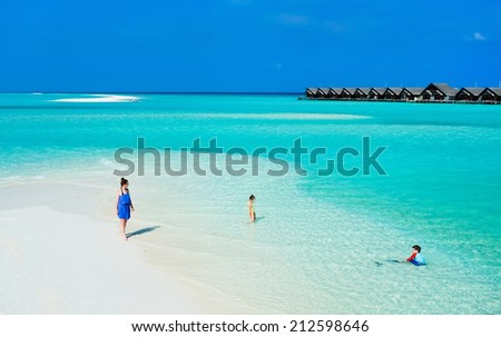 Aerial view of mother and kids enjoying tropical beach vacation - stock photo
