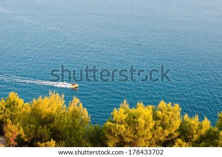 Aerial view of motorboat sailing through beautiful blue Adriatic Sea in Montenegro  - stock photo