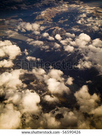 Aerial view of mountain range with snow capped peaks in late afternoon light