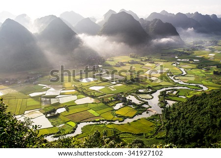 Aerial view of multiple mountain peaks and rice field in Vietnam - stock photo