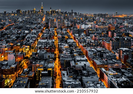 Aerial view of New York City at night with illuminated avenues converging towards midtown. - stock photo
