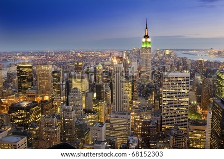 Aerial view of New York City displaying a spectacular skyline as the buildings light up - stock photo