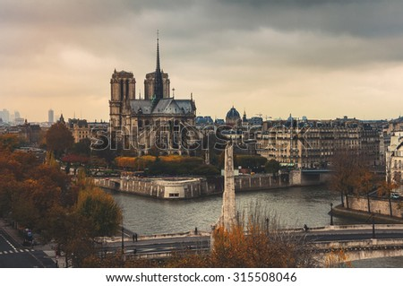 Aerial view of Notre Dam with Seine river in autumn. Cloudy sky, grey toning