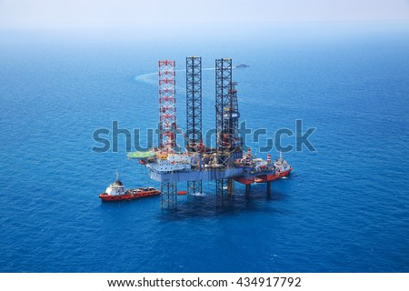 Aerial View of Offshore Jack Up Drilling Rig in The Middle of The Ocean:Selective focus with shallow depth field.    - stock photo