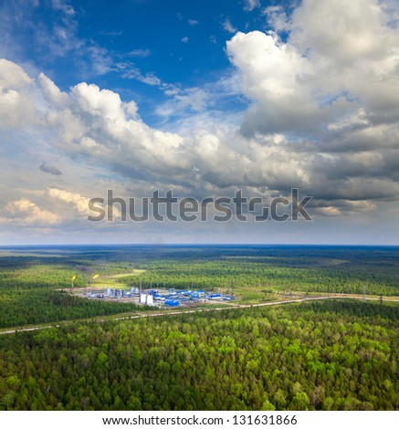 Aerial view of oil production station which located in dense forest during the summer day. The torch is on the high pipe. It is flaring gas here. - stock photo