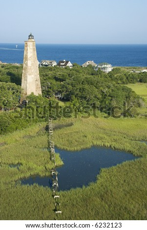 Aerial view of Old Baldy lighthouse in marshy lowlands of Bald Head Island, North Carolina. - stock photo