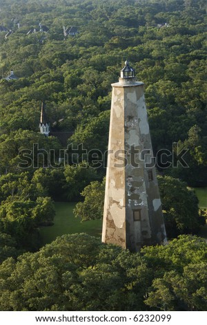 Aerial view of Old Baldy lighthouse in wooded park at Bald Head Island, North Carolina. - stock photo
