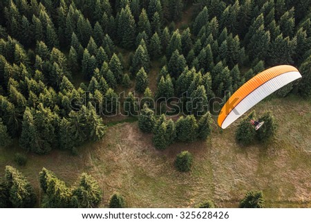 aerial view of paramotor flying over the forest in Poland - stock photo