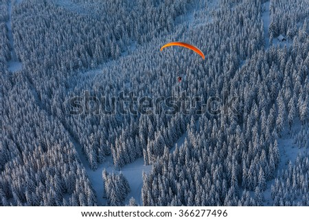 aerial view of paramotor flying over the forest in winter in Poland - stock photo