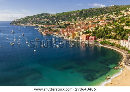 Aerial view of picturesque French Riviera mediterranean coast with medieval town Villefranche-sur-Mer, sandy beach and leisure boats anchored in harbor. - stock photo