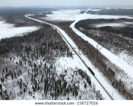 Aerial view of pine forest during a winter day. Freight diesel train passing the snowy forest  - stock photo