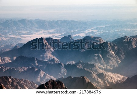 Aerial view of remote mountain ranges with jagged peaks in Egypt stretching back into the distance in a beautiful tranquil landscape - stock photo