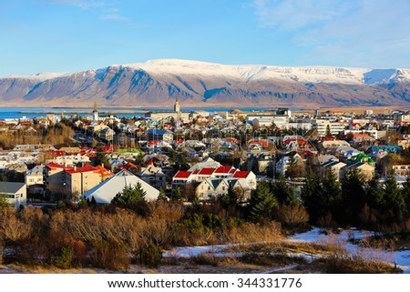 Aerial view of Reykjavik, Iceland with snow capped mountains in the background - stock photo