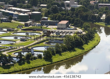 Aerial view of river meandering around sewage water treatment plant