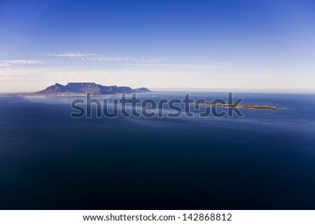 Aerial view of Robben Island with Table Mountain in the distance, Cape Town; South Africa. Former South African President, Nelson Mandela, was held here as a political prisoner for 27 years. - stock photo