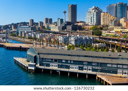 Aerial view of Seattle waterfront and skyline with the Space Needle in the background. There's traffic on the waterfront Alaskan Way Viaduct, the elevated double-decker Highway 99. - stock photo