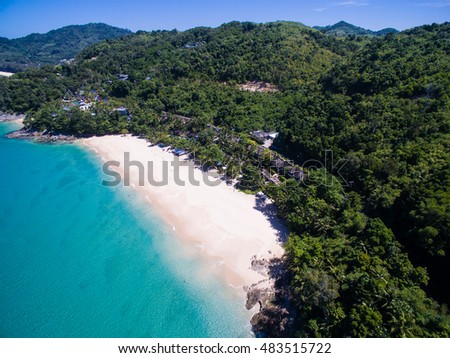 Aerial view of small white sand beach with blue clear sea water, blue sky, green trees and some people on the beach. White Beach, Phuket, Thailand.