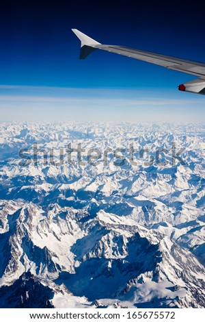 Aerial view of snow capped Alps mountains between Switzerland and Italy - stock photo