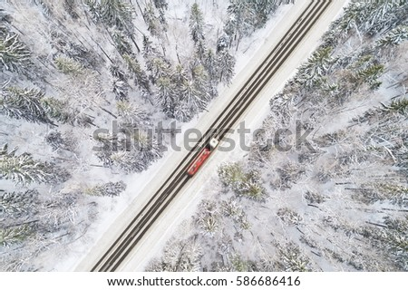 Aerial view of snow covered road in winter forest, truck passing by, motion blur