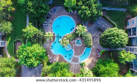 Aerial view of swimming pool in a typical multi-level apartment living in Houston, Texas, US at sunset. It surrounded by green garden, foldable chairs furniture and unidentified swimming kids. - stock photo