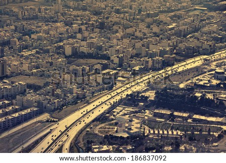 Aerial view of Tehran with a main highway lit under sunlight.  - stock photo