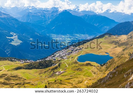 Aerial view of the Bettmersee (Lake) and the Bettmer town, with the numerous peaks of alps as background, in Valais, Switzerland, near the famous Aletsch glacier - stock photo