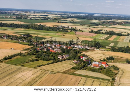 aerial view of the blue sky  and village harvest fields in Poland - stock photo