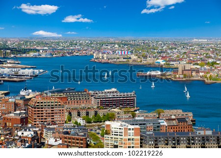 Aerial view of the Boston harbor and waterfront on a beautiful sunny day. Colorful, bright image with blue sky and white clouds. - stock photo