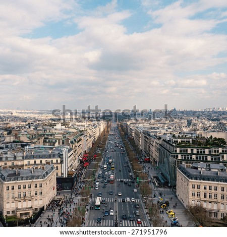 Aerial view of the city and Champs Elysees with blue cloudy sky from the Arc de Triomphe, Paris. - stock photo