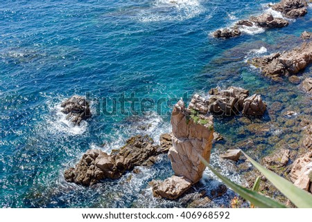 Aerial view of the cliffs of the Catalan coast, where you can see wild marine life, seagulls nest on the cliffs and the waves break hard on the rocks, a calm sea and sunny sky - stock photo