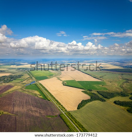 Aerial view of the countryside with fields of crops in summer. - stock photo