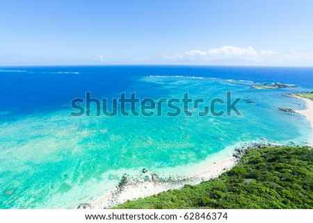 Aerial view of the deserted beach on the tropical island with vast coral reef and clear blue sea, Kume Island, Okinawa, Japan - stock photo