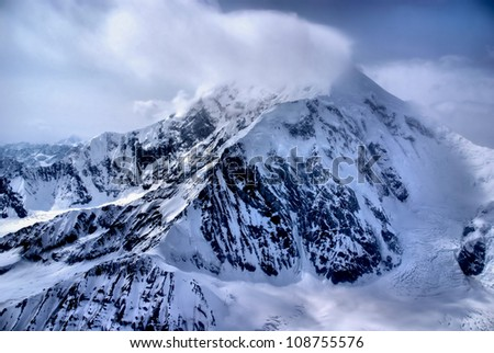 Aerial View of the Great Mount McKinley (Denali) Peak in the Alaskan Wilderness, Denali National Park, AK.  Snow and clouds forming/blowing off the peak.  A Beautiful Snowscape of Rock, Snow, and Ice. - stock photo