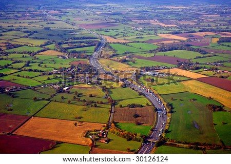 Aerial view of the M56 highway, running through the Cheshire countryside. This is a major highway in the North of England and runs to the city of Manchester. - stock photo