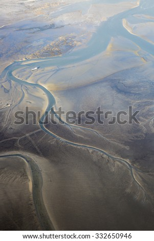 aerial view of the mudflat coastline at low tide with water winding in the mud and sand bank, Frisian island Ameland, The Netherlands - stock photo