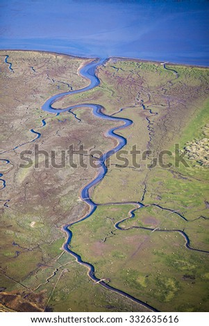 aerial view of the mudflat coastline at low tide with water winding through the mud, dunegrass and sand bank, Frisian island Ameland, The Netherlands - stock photo
