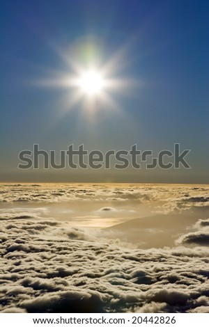 Aerial view of the setting sun above a blanket of clouds.