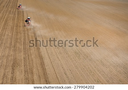 Aerial view of the the tractor harrowing the large brown field in spring season