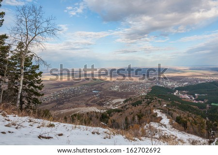 Aerial view of the town, trees, snow, forests, agricultural fields, farms and villages in the fall. - stock photo