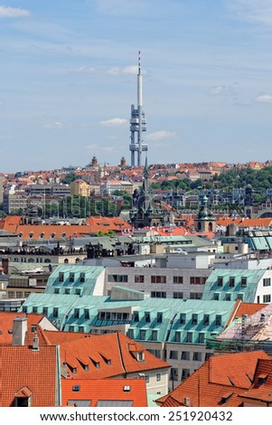Aerial view of the traditional red roofs of the city of Prague, Czech Republic with the Television tower in the distance. With its 216 m in height, it's the tallest building in the city. - stock photo